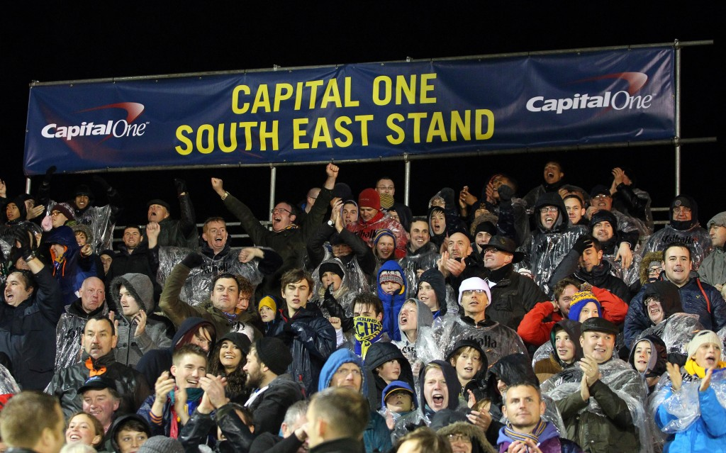 Shrewsbury Town FC fans cheer on their team from one of the temporary stands funded by Capital One.