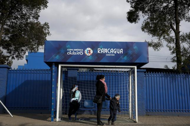 People wait for transportation in a bus stop decorated as a soccer goalpost, outside El Teniente stadium, in Rancagua
